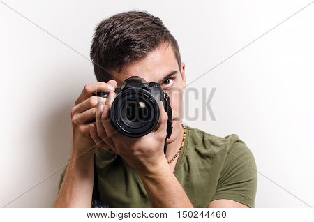 Young photographer taking a shot. Isolated. White background.