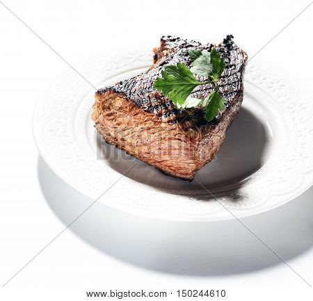 fried steak with parsley on a white background
