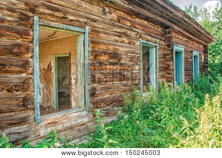 log wall of old abandoned wooden house on sunny summer day