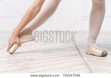 Close-up Legs Of Young Ballerina On The Wooden Floor In White Interior