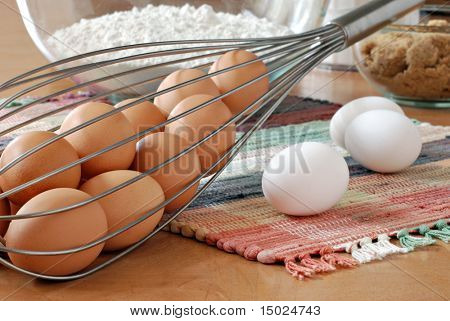 Kitchen still-life of large  whisk filled with fresh brown eggs.  Flour and brown sugar in soft focus in the background.