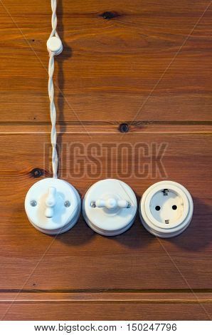 Old fashioned electricity switchs electric wire and power point plug on a wooden wall