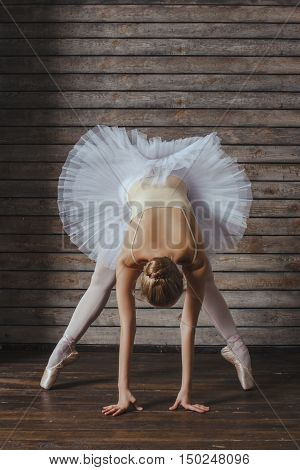 Beautiful Young Woman Ballerina Stretching Warming Up On The Background Of Wooden Wall