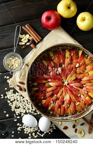 Raw Traditional Homemade German Apple Pie Cake With Nuts And Cinnamon In Form For Baking On Dark Woo