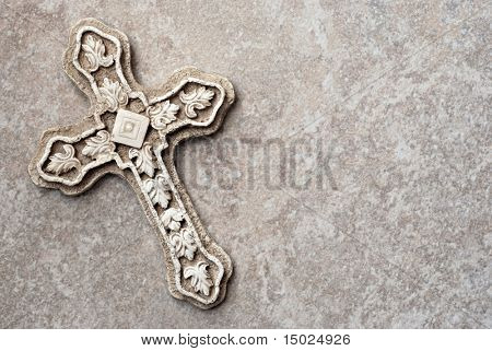 Ornate stone cross on marble background with copy space.