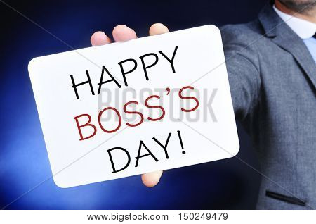 a young caucasian businessman shows a signboard with the text happy boss day written in it