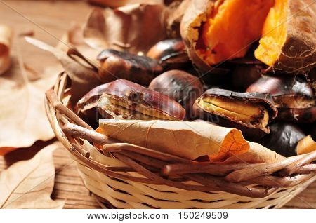 some roasted chestnuts and some roasted sweet potatoes in a wicker basket with autumn leaves, on a rustic wooden table