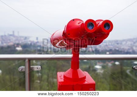 red binoculars for viewing. view of the city from a height