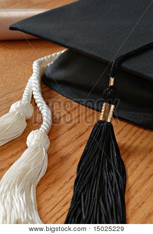 Graduation cap with honor cords and diploma on wood background.  Macro with shallow dof.  Selective focus on tassel.
