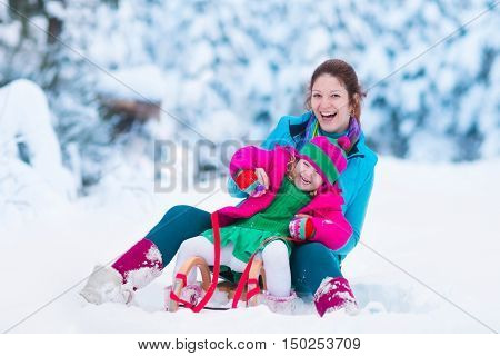Young mother and little girl enjoying sleigh ride. Child sledding. Toddler kid riding sledge. Children play outdoors in snow. Kids sled in snowy park. Outdoor winter fun for family Christmas vacation.