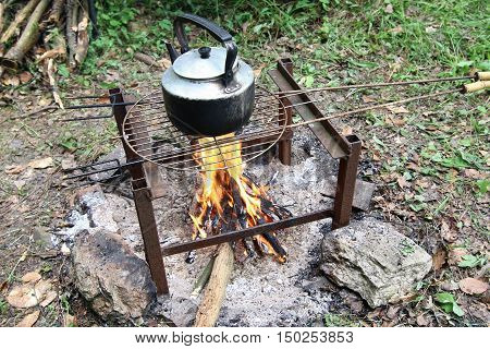 Making tea on the camp fire - teapot on fire