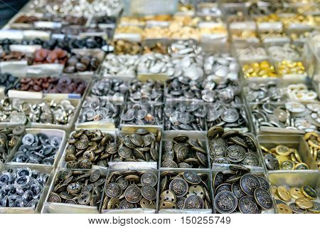 Vintage clothes buttons in silver and gold colouring for sale in the most famous flea market in Chinatown district, Bangkok, Thailand