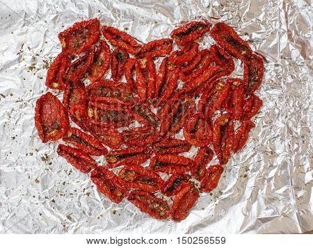 sun-dried tomatoes in a heart shape. sun dried tomatoes on a foil. background of dried tomatoes with basil and olive oil on the aluminum foil. top view