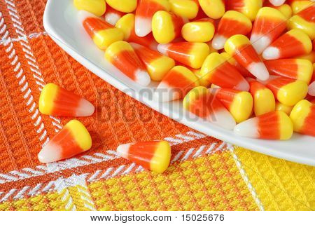 Candy corn on glass plate with color coordinated fabric background.  Macro with shallow dof.  Focus on 3 candies on fabric.