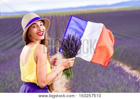 Young woman standing with lavender bouquet and french flag on the lavender field in Provence in France