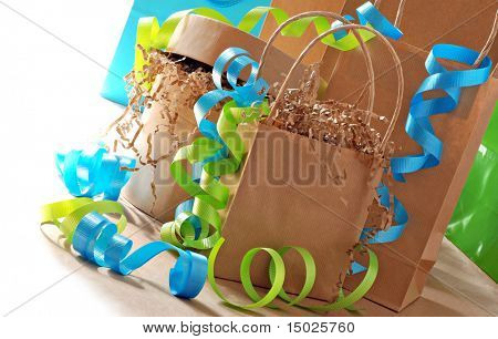 Simple brown paper gift bags and boxes decorated with colorful curling ribbon.  Bright white background.