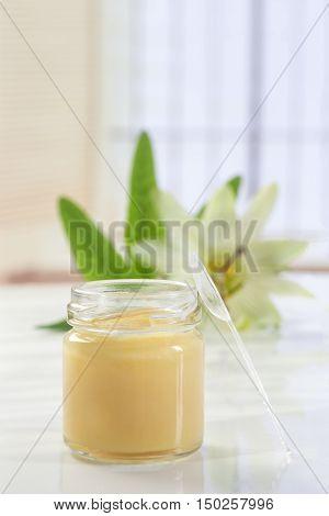 raw organic royal jelly in a small bottle with flowers