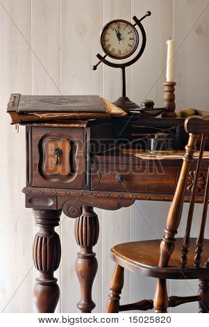 Still life of antique secretary desk from the early 1900s with vintage accessories.  Soft natural side lighting shows details including nicks and scratches from wear.