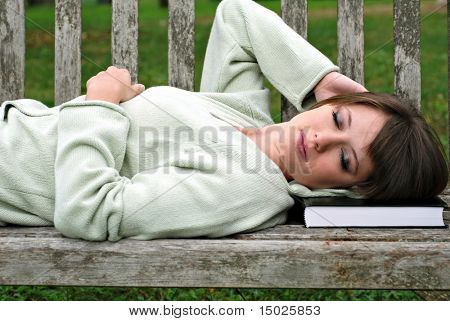 Beautiful female college student asleep on park bench after studying.  Close-up with shallow dof.