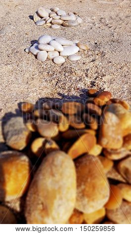 Thre piles of round stones laying on the sand.