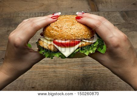 Eating hamburger. Delicious hamburger in the hands. Fastfood meal.
