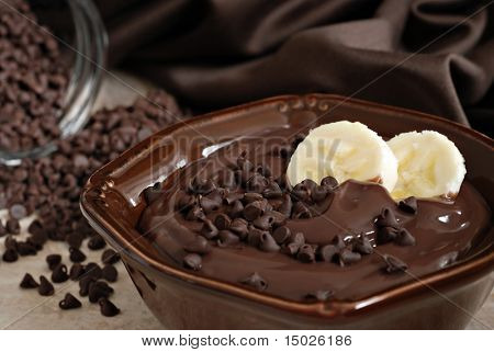 Delicious creamy chocolate pudding topped with chocolate chips and banana slices. Still life with extremely shallow dof.  Selective focus on banana.