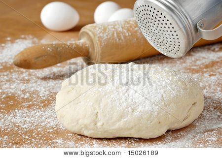 Classic wooden rolling pin with freshly prepared dough and retro flour shaker.  Shallow dof.  Selective focus on shaker and dough.