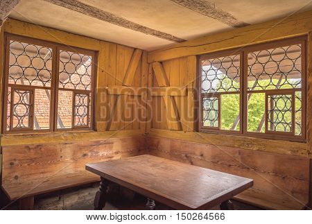 Rustic dining corner interior - Retro style dining room interior with wooden table walls and benches depicting the rural life in the past.