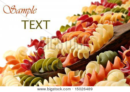 Colorful pasta with wooden spoon on white background.  Copy space included.