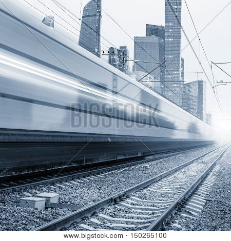 Modern high-speed train moves fast on the business center background.