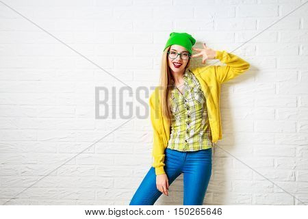 Funny Hipster Girl at White Brick Wall Background. Street Syle Teenage Going Crazy. Trendy Casual Fashion Outfit in Spring or Autumn. Copy Space.
