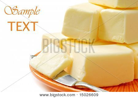 Fresh creamy real butter on plate with knife on white background with copy space.