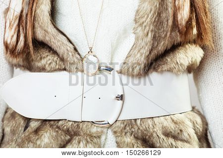 Winter time fashion for women. Woman wearing sweater fur vest belt and pendant in freezing cold time.