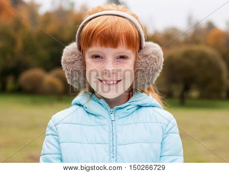 Close up cute ginger girl in the earmuffs smiling autumn trees behind