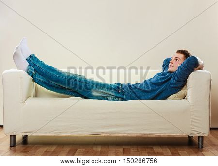 Home leisure concept. Young handsome man relaxing on couch laying and dreaming