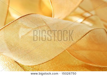 Holiday background image of metallic gold ribbon  curls on shiny  wrapping paper.   Macro with shallow dof.