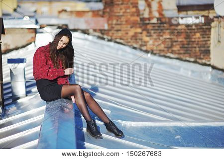 Cute long-haired girl sits on the iron roof of the house on a bright Sunny day against a brick wall.