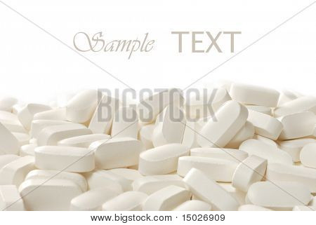 Cream colored nutritional supplements (calcium, magnesium, vitamin d) on white background with copy space.  Macro with shallow dof.