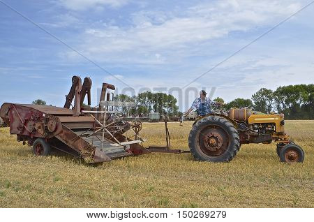 ROSHOLT, SOUTH DAKOTA, August 21, 2015: An unidentified man driving a Minneapolis Moline tractor and McCormick combine at the annual Rosholt Area Threshing Bee held the third full weekend of August.