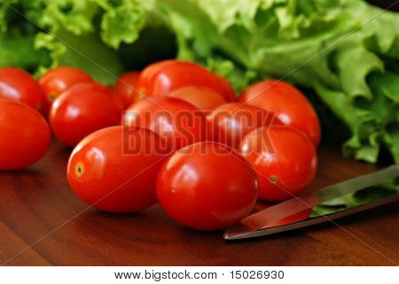 Small grape tomatoes and leaf lettuce on wooden cutting board with knife.  Macro with shallow dof.