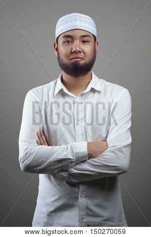 Young muslim man Isolated on grey background