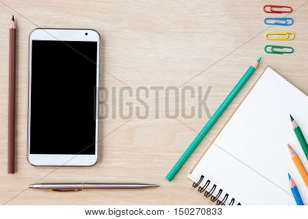 blank paper, pen, color pencil, and smart phone on wood desk / can you write text message / copy space / top view