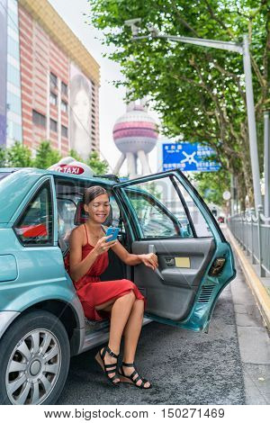 Asian woman taking a taxi cab ride paying her fare using an online mobile payment app via smartphone. Businesswoman in business center financial district in Pudong, Shanghai, China.