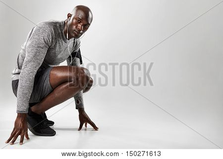 Healthy Young Black Man Kneeling On Grey Background