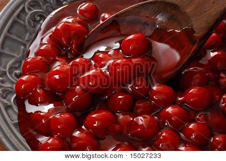 Delicious dessert cherries in decorative bowl with wooden spoon.