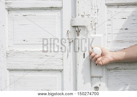 horizontal close up image of a caucasian man's hand opening a pure white rustic double door with white door knob.