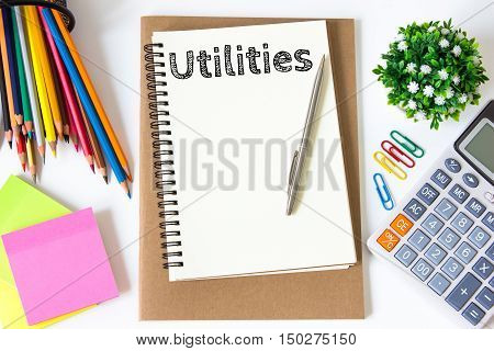 utilities text message on white paper and office supplies, pen, paper note, on white desk , copy space / business concept / view from above, top view