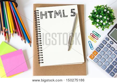html 5 text message on white paper and office supplies, pen, paper note, on white desk , copy space / business concept / view from above, top view