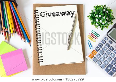 giveaway text message on white paper and office supplies, pen, paper note, on white desk , copy space / business concept / view from above, top view
