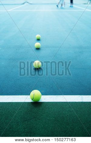 Tennis court with tennis balls intentionally shot with surreal dramatic tone. Shallow depth of field.